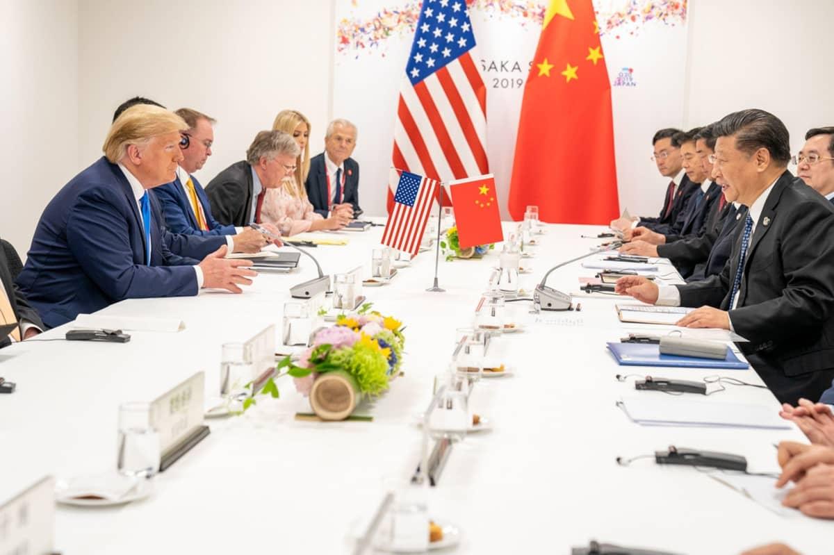 Trump ja Xi seurueineen istuvat pöydän ääressä.
