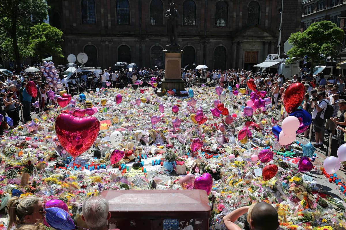 Suuri määrä kukkia ja ilmapalloja. Ympärillä ihmisiä.