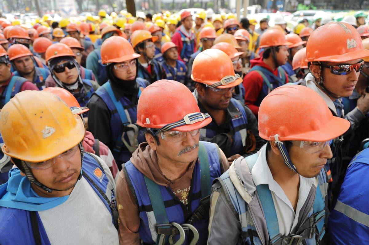 Suuri ihmisjoukko seisoo suojakypärät päässä.