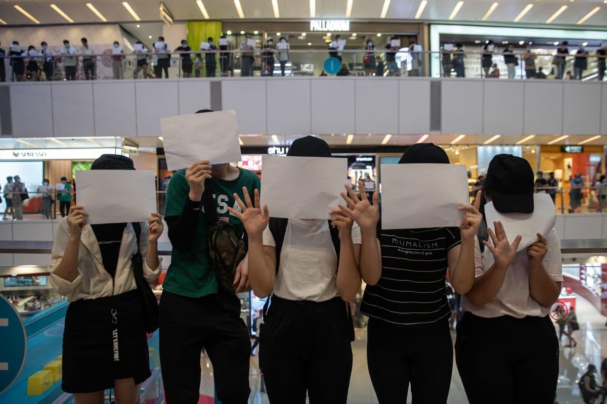 Mielenosoittajia valkoiset paperiarkit kasvojensa edessä
