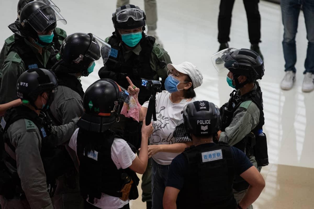 Mellakkapoliisit piirittävät ostoskeskuksessa naista, jolla on kasvosuojus ja joka heristää sormeaan poliiseille.