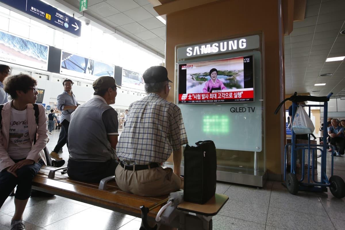 TV:ssä näkyy pohjoiskorealainen uutistenlukija. Ihmiset ovat ilmeisesti juna-asemalla, seuraavat uutista.