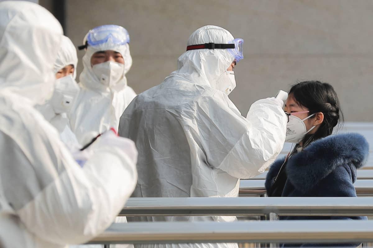 Turvallisuushenkilökunta mittaa metromatkustajien lämpötilan metron sisäänkäynnillä Pekingissä.