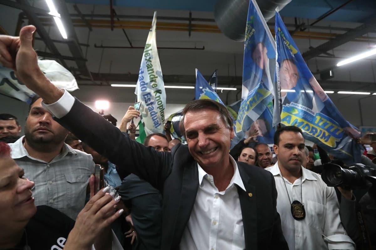 Mies puku päällään hymyilee ja näyttää peukaloa ylös päin, taustalla miehiä lippujen kanssa.