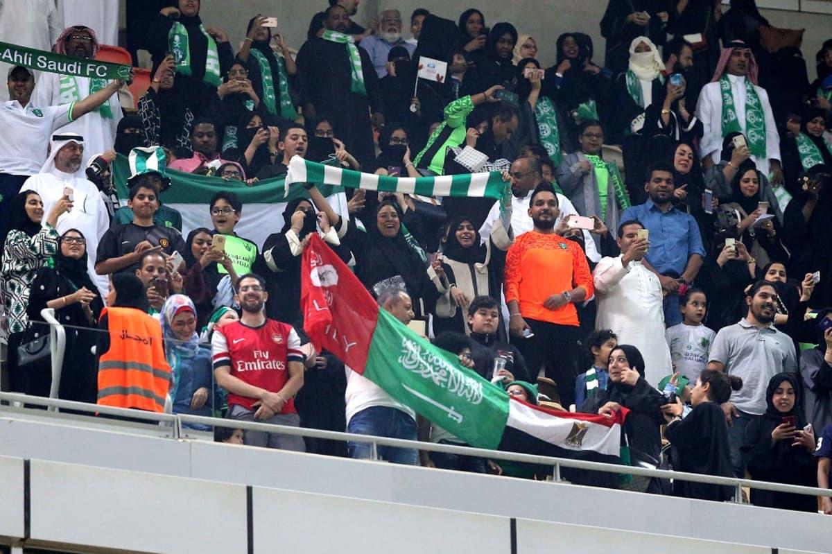 Jalkapallokatsomossa hurrataan ja heilutetaan joukkueen värejä. Miesten joukossa on naisia mustissa abaya-kaavuissa.