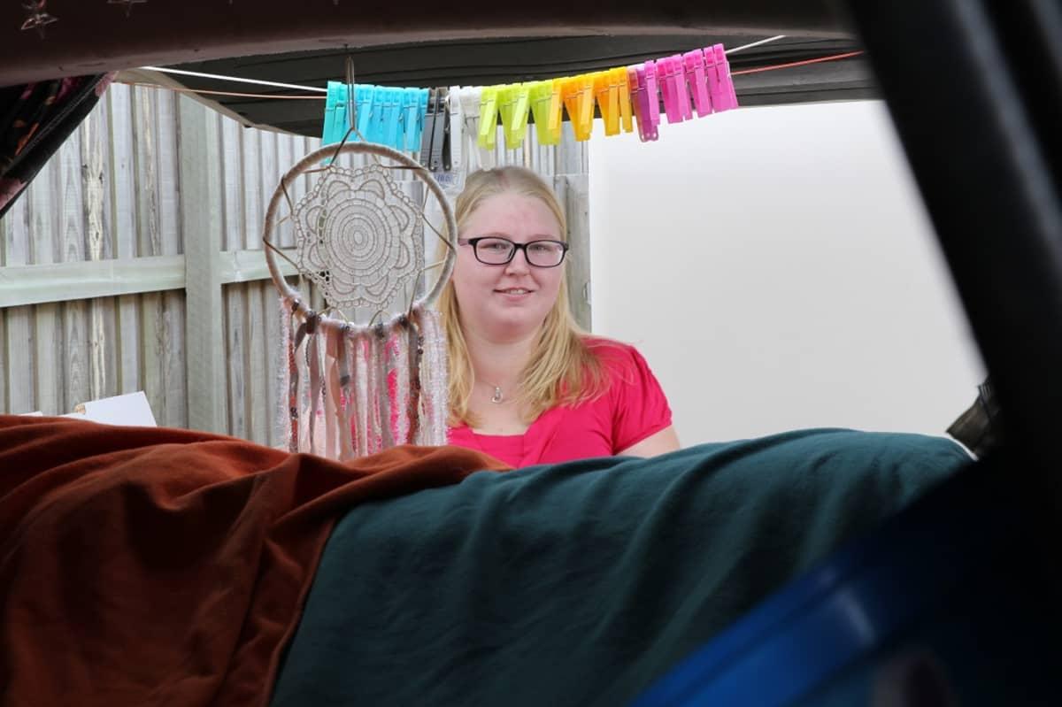 Kuvassa Emmi Vinberg kuvattuna pakettiauton takana. Auton takaosassa pyykkinaru, jossa pyykkipoikia.