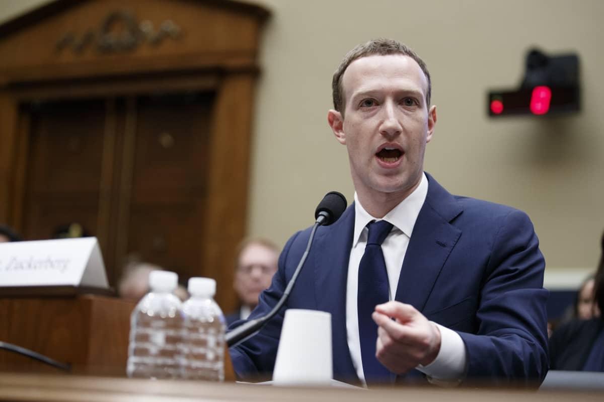 Tummansiniseen pukuun, valkoiseen kauluspaitaan ja tummansiniseen kravattiin pukeutunut Zuckerberg istuu pöydän takana ja puhuu mikrofoniin. Taustalla näkyy iso ovi. Pöydällä on kaksi vesipulloa.