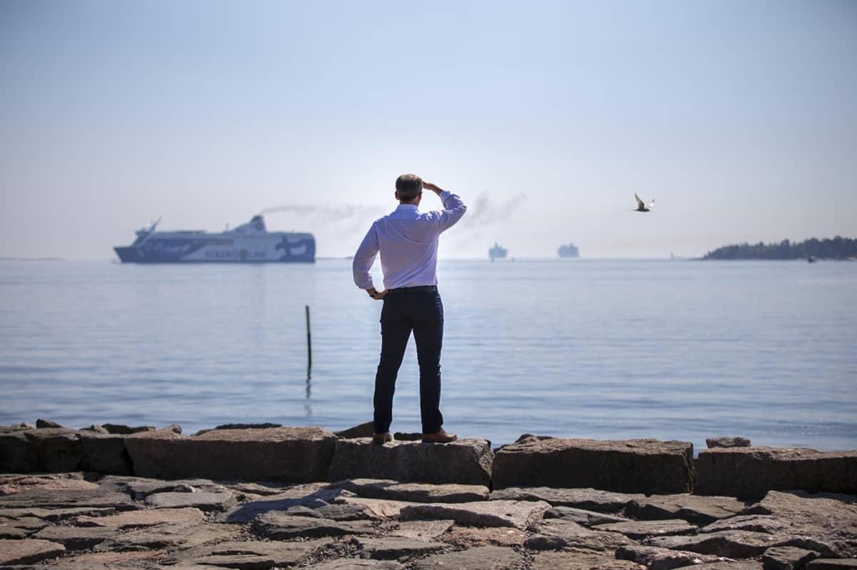 Mies selin rannassa, tähyää merelle, jossa ohi menossa Eckerön Finlandia-lautta.