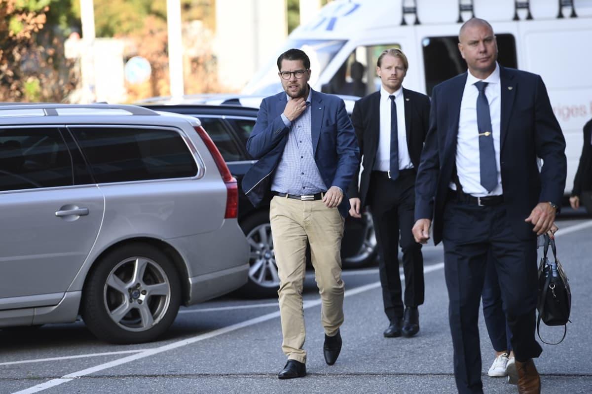 Åkesson kävelee kadulla yllään sininen takki, vaaleansininen kauluspaita ja jalassaan beessit housut, musta kengät. Vierellä kulkee turvamiehen näköisiä miehiä mustissa puvuissa.