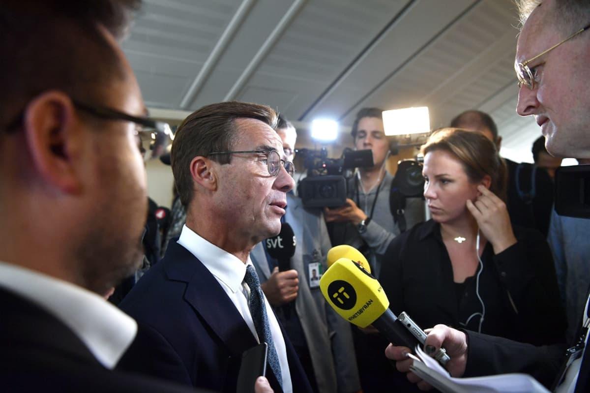 Tummaan pukuun, kauluspaitaan ja kravattiin pukeutunut silmälasipäinen Kristersson seisoo toimittajien keskellä ja puhuu häntä kohti osoitettuihin mikrofoneihin.