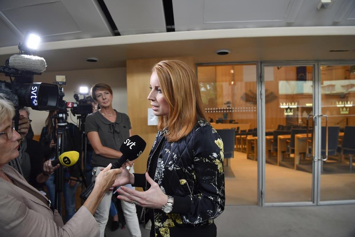 Lööf puhuu salissa toimittajajoukolle. Etualalla on Ruotsin television SVT:n toimittaja pitelemässä mikrofonia. Lööfillä on tumma kukkakoristeinen asu.
