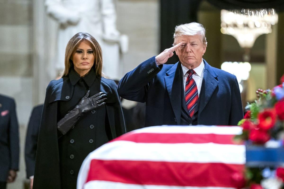Kuvassa Yhdysvaltain presidentti Donald Trump ja hänen vaimonsa Melania Trump arkun vieressä. Presidentti tekee kunniaa oikealla kädellään ja jänen puolisonsa pitää kättään sydämensä kohdalla.