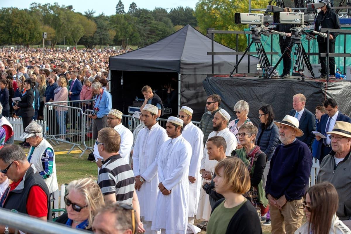 Suuri väkijoukko seisoo kentällä puistossa.