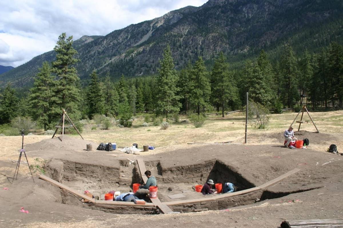 Arkeologeja kaivamassa kivirakennuksen raunioita. Taustalla korkeita vuoria.
