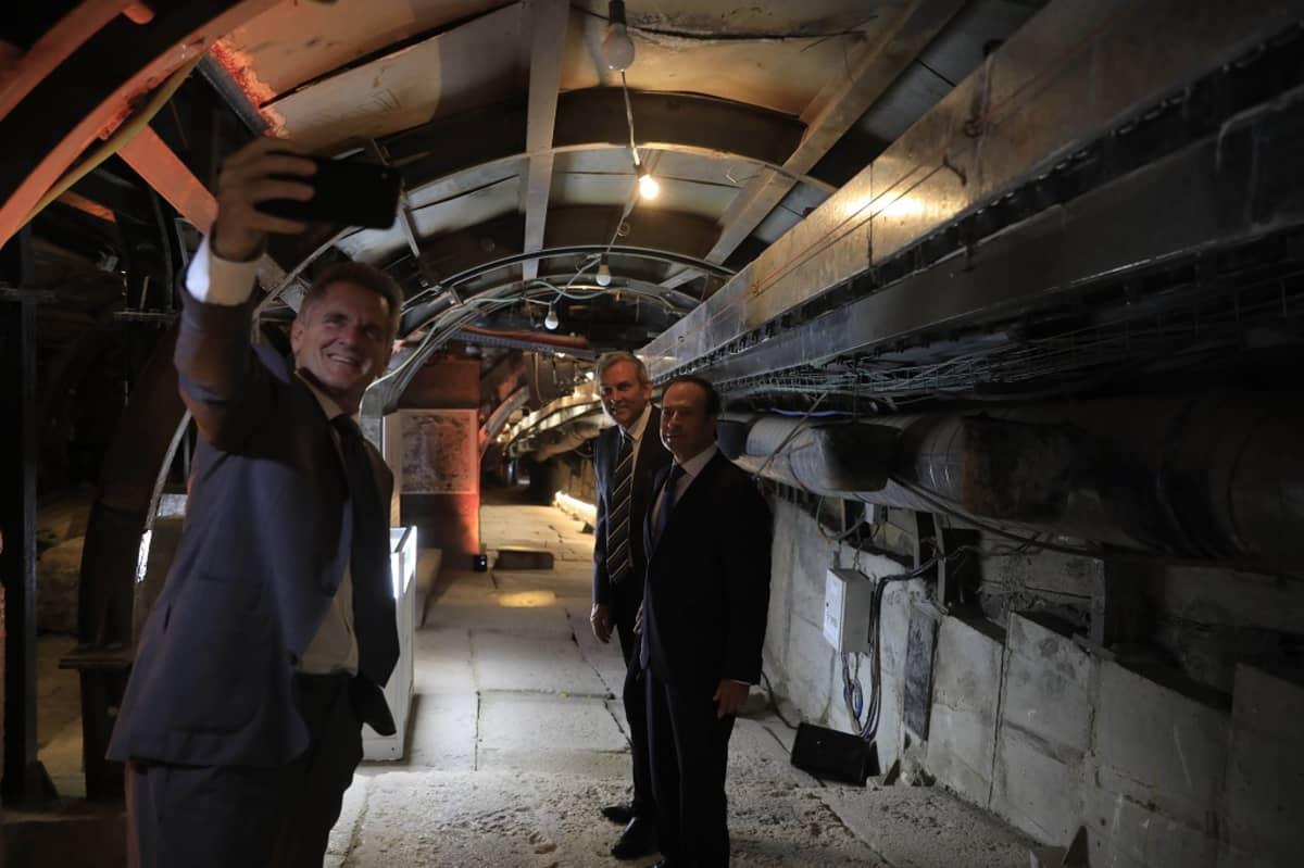 Kolme miestä tunnelissa, etummainen ottaa kännykällä selfietä.