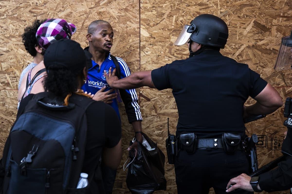 Kuvassa vasemmalla mustaihoinen mies. Selin kameraan oleva valkoihoinen poliisi on ojentanut kätensä kohti miestä.