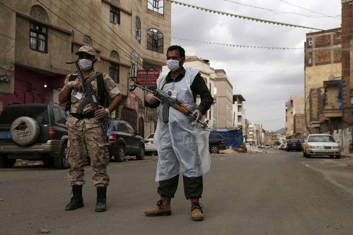 Kuvassa kaksi sotilasta seisoo kadulla. Molemmilla on aseet ja hengityssuojaimet kasvoillaan.