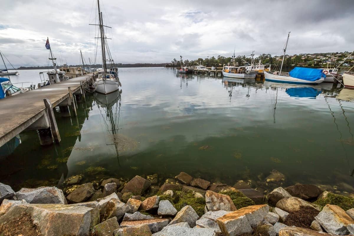 Kivikkoinen ranta ja laituri. Satamaan on ankkuroitu pieniä kalastusaluksia.