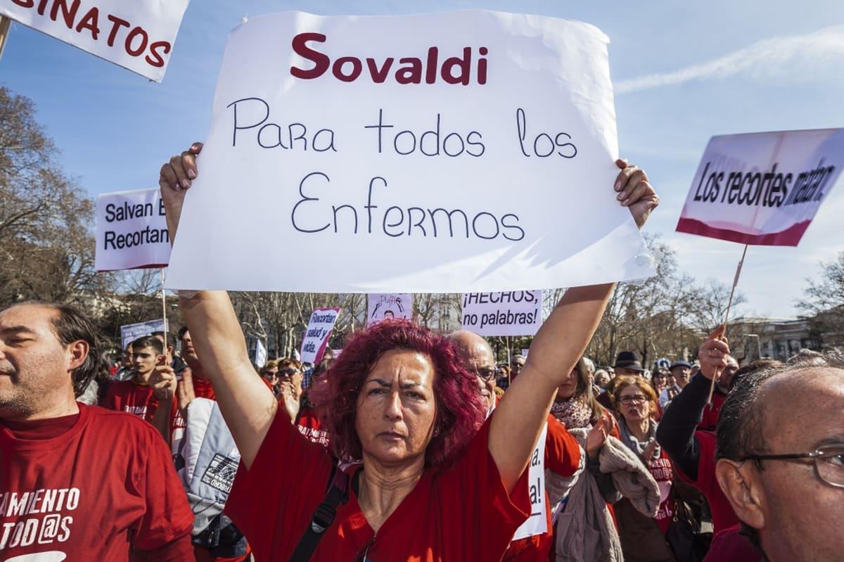 """Mielenosoittajia, joiden kylteissä lukee espanjaksi """"Sovaldia kaikille sairaille"""" ja """"Tekoja, ei sanoja!"""""""