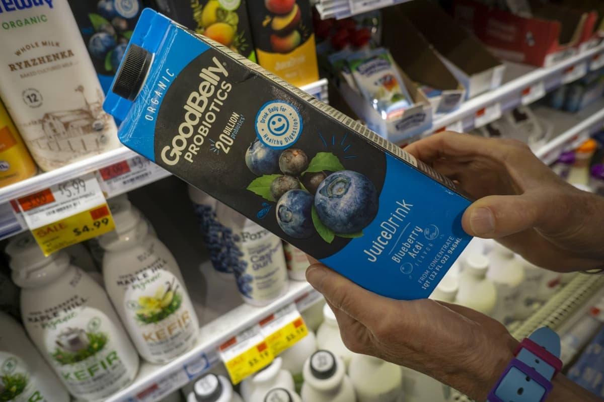 Good Belly Probiotics -mustikkamehupurkki asiakkaan kädessä, taustalla hyllyissä muuta ruokaa.