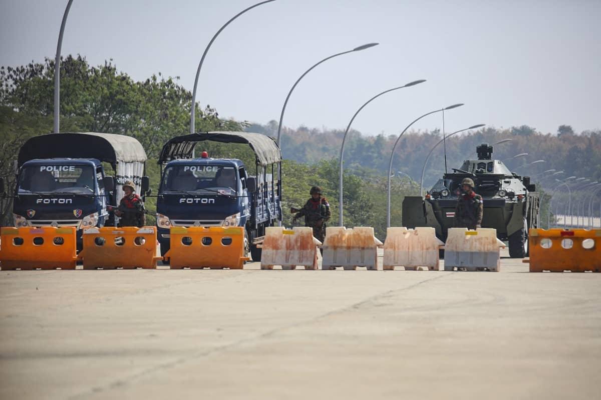 Kuvassa tiesulku, jonka takana on kaksi armeijan autoa ja sotilasajoneuvo.