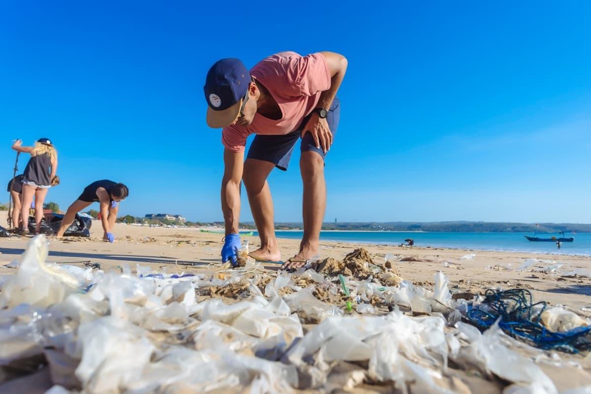 Neljä ihmistä poimii muovipusseja ja muita muoviroska hiekkarannalta.