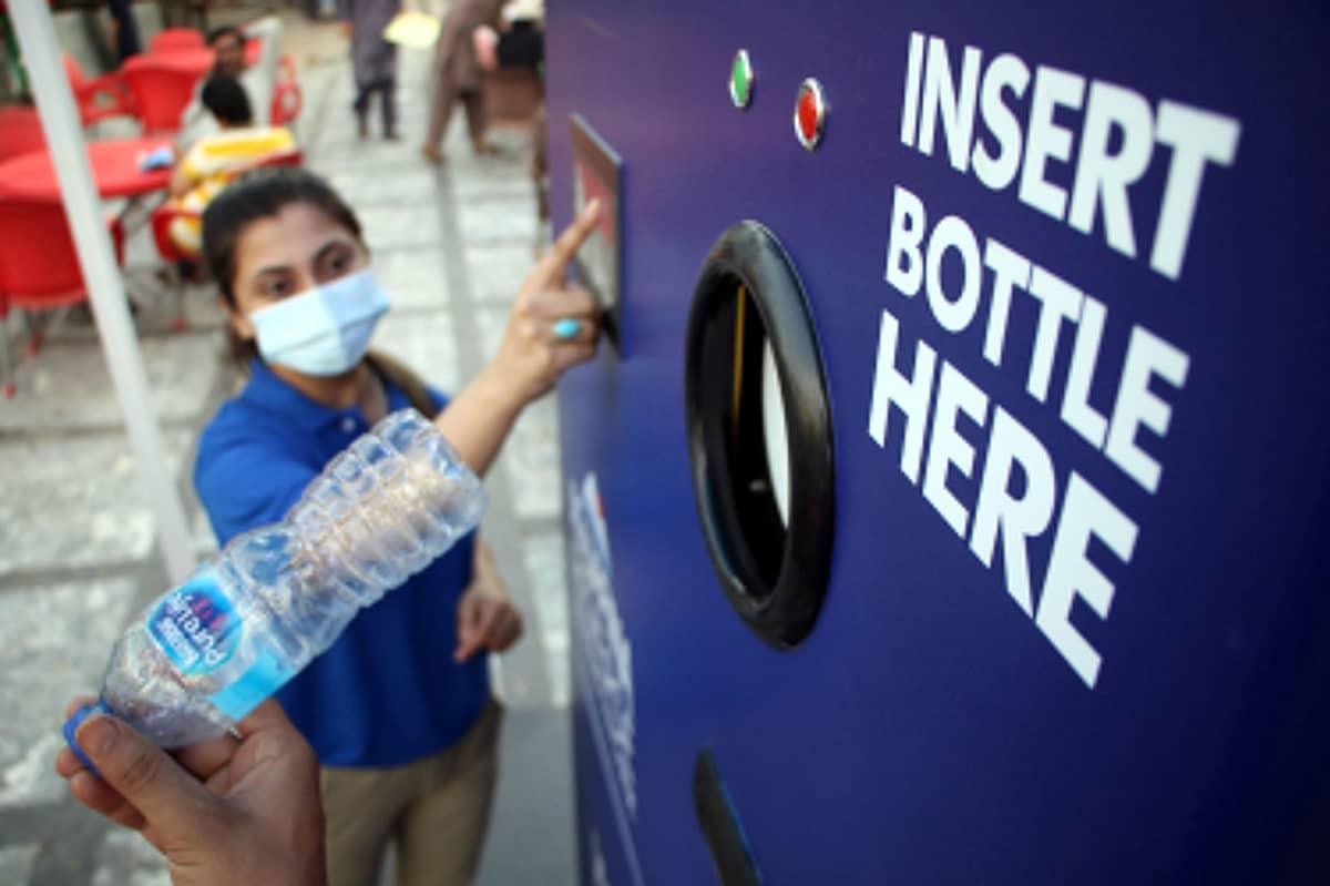 Kasvomaskia pitävä nainen pullonpalautusautomaatilla.