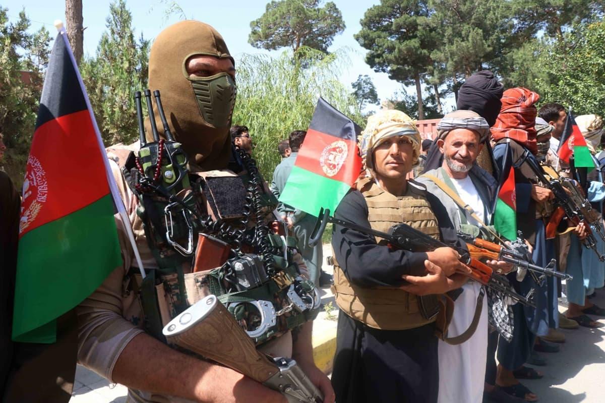 Kuvassa etualalla kasvonsa naamioilla peittänyt sotilas. Hänen vieressään seisoo kaksi aseistautunutta siviilimiestä.