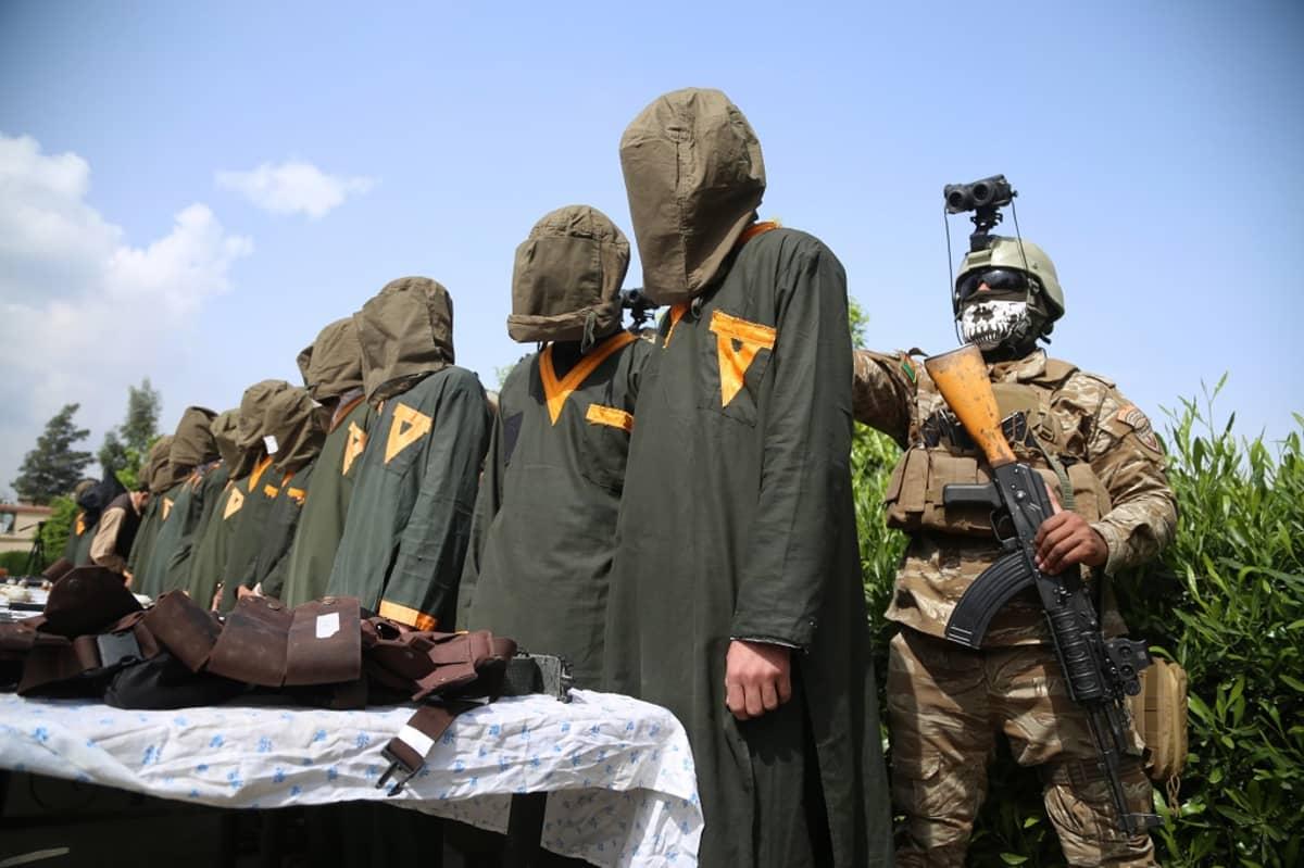 Kuvassa useita pidätettyjä seisomassa huppu päässä. Heidän takanaan on sotilas rynnäkkökivääri kädessään.