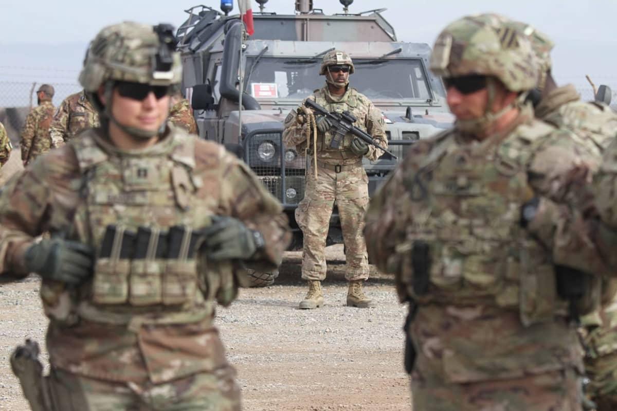 Kuvassa etualalla kaksi amerikkalaista sotilasta. Taustalla näkyy armeijan ajoneuvo ja sotilas.