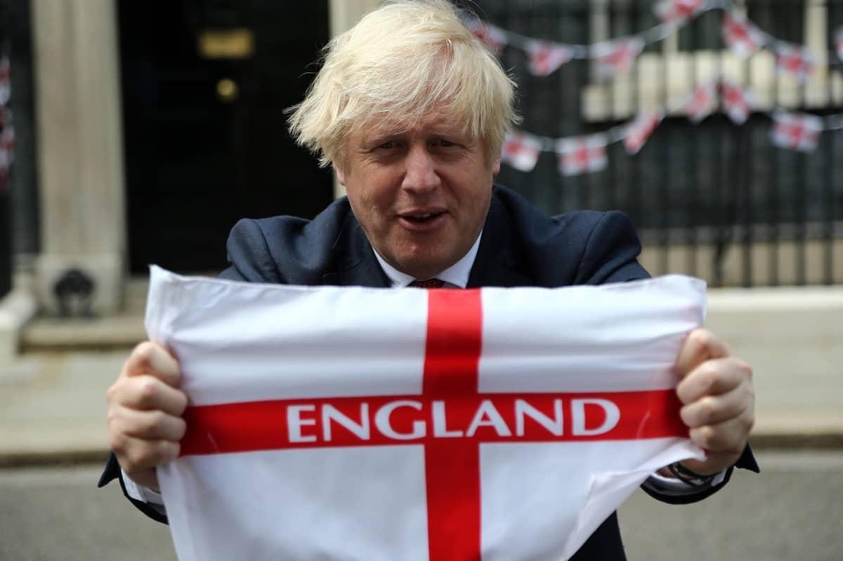 """Boris Johson pitelee Englannin punavalkeaa ristilippua, jossa lukee """"England"""". Taustalla kaiteeseen kiinnitetty lippujono."""