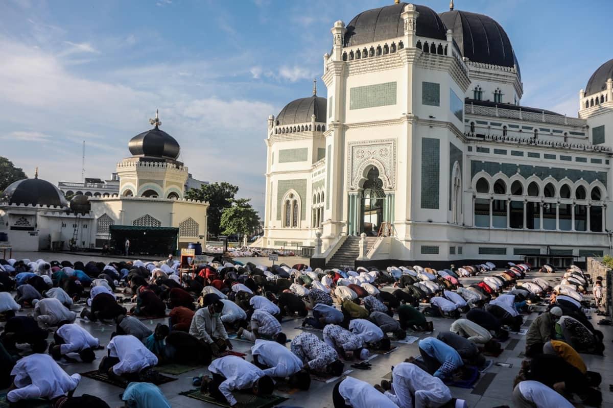 Rukoukseen kumartuneita miehiä riveissä moskeijan pihalla.