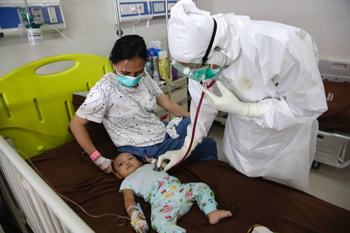 Vauva makaa sairaalasängyssä, äiti istuu sängyssä, suojavarusteinen lääkäri tutkii lasta.