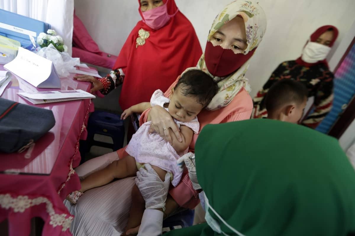 Vauva äitinsä sylissä terveystyöntekijöiden ympäröimänä.