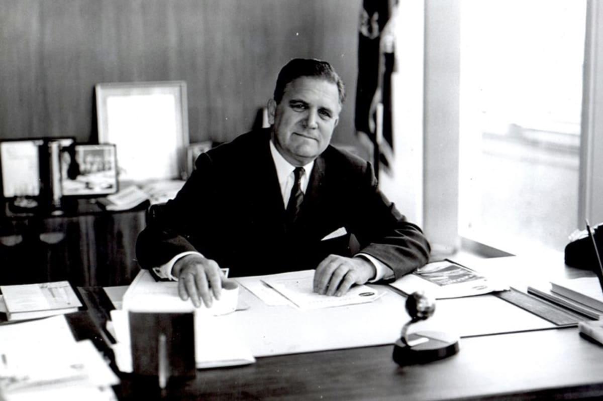 Mustavalkoinen kuva miehestä työpöydän takana.