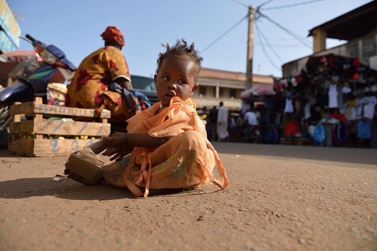 Pieni lapsi leikkii kadulla.