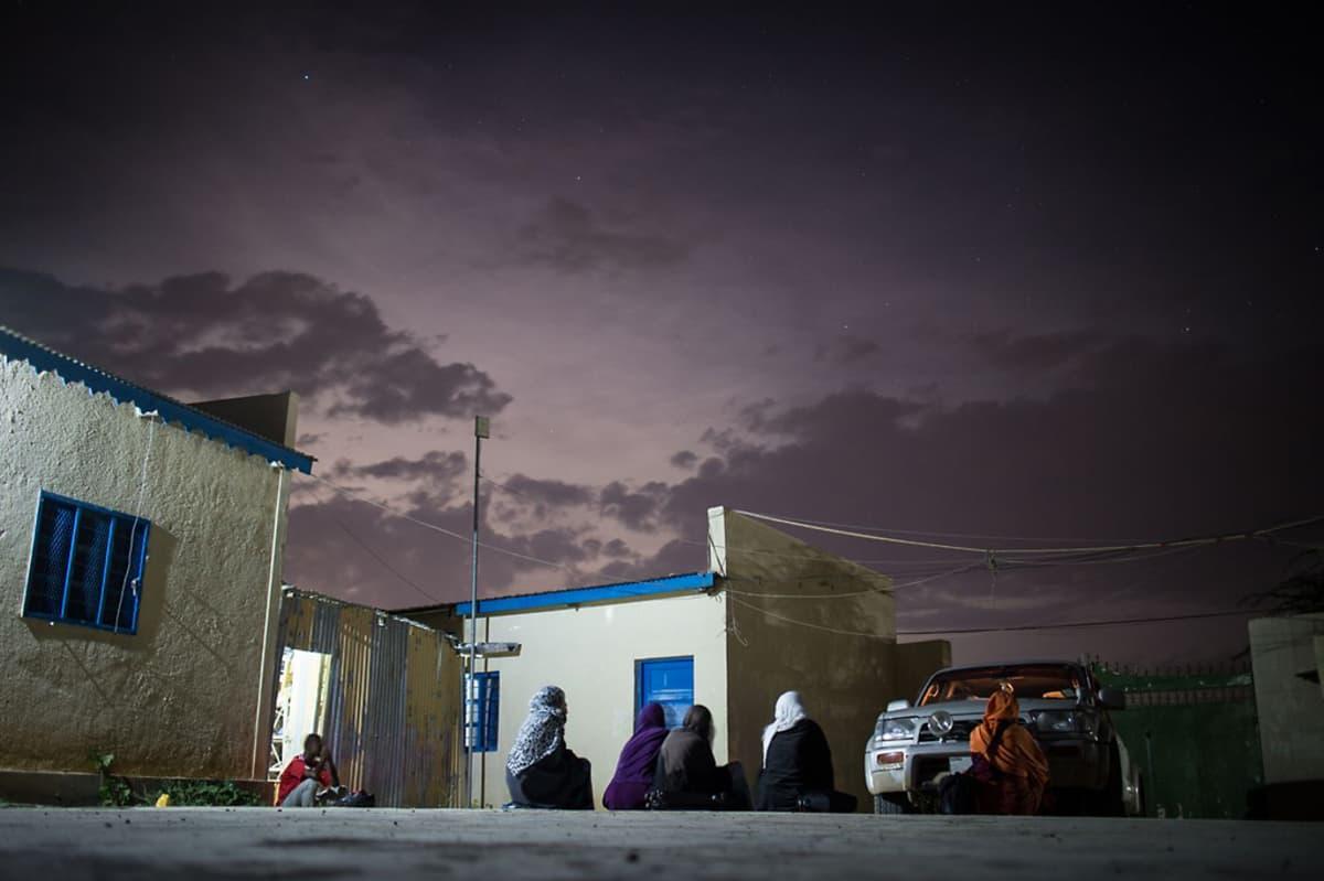 Tytöt levähtävät SOCSA Centerin pihassa pitkän päivän jälkeen. Yö laskeutuu, taivaalla on enää hento auringon kajo.