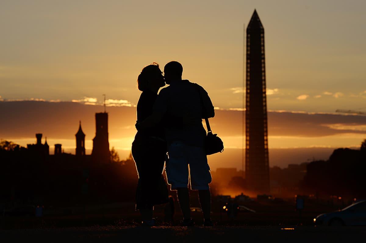 Pariskunta suutelee Washington-monumentin edustalla.