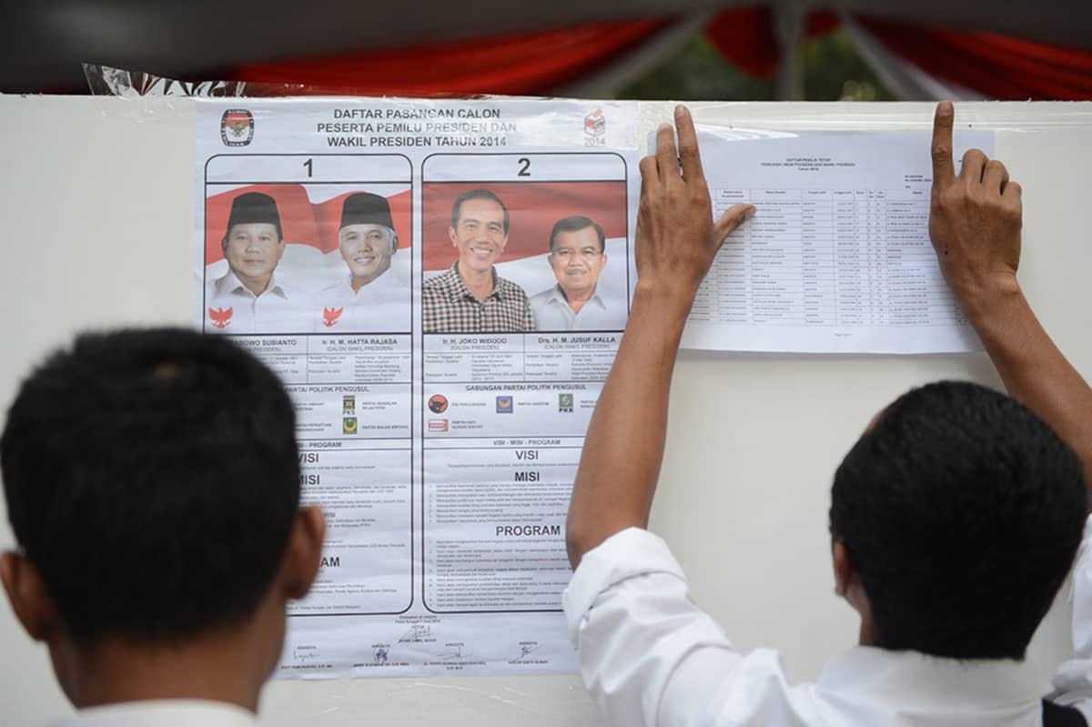 Vaalivirkailijat kiinnittävät ehdokkaita esittäviä julisteita seinään äänestyspaikalla Jakartassa 9. heinäkuuta 2014.