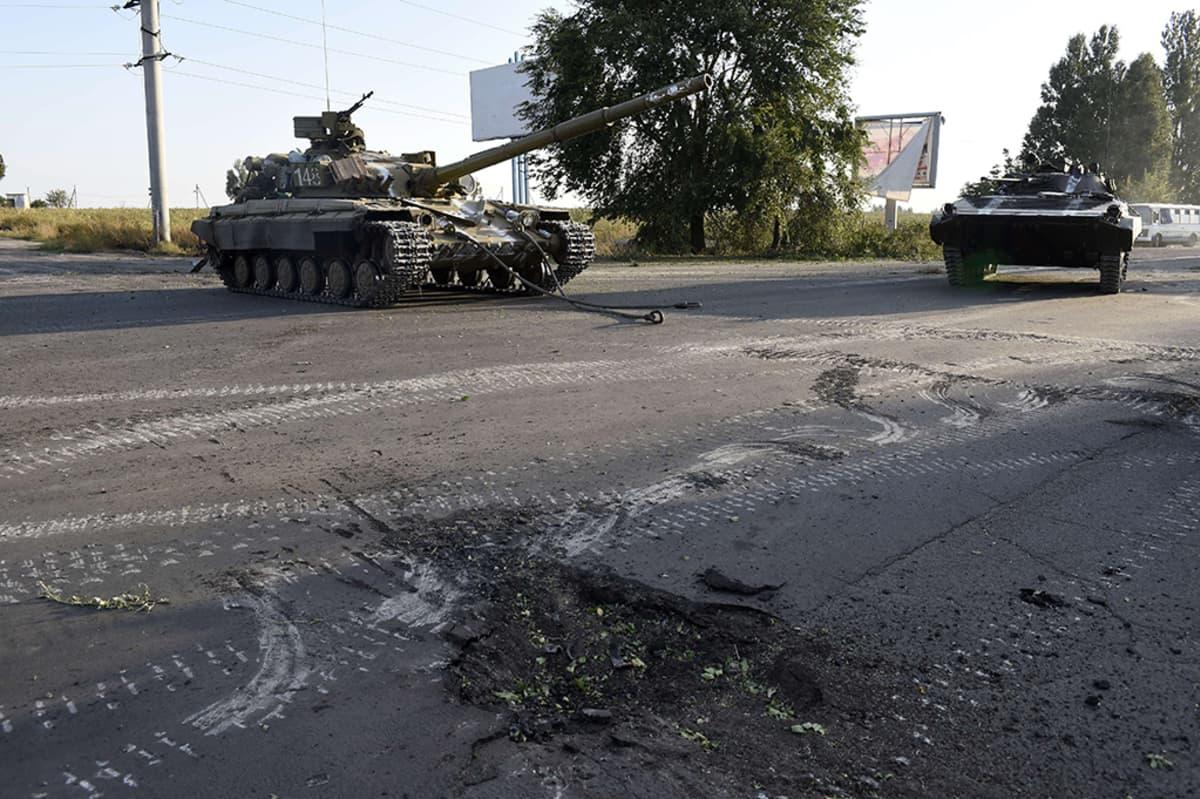 Ukrainalaistankkeja vartiossa yöllisten pommitusten jälkeen Venäjälle johtavan tien varrella Mariupolin lähistöllä 7. syyskuuta 2014.
