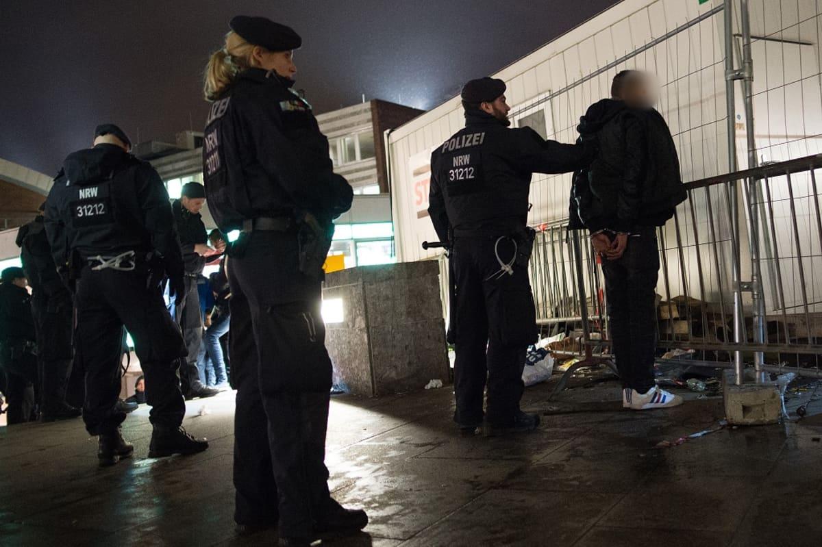 Kolme poliisia ja pidätetty, jolla on käsiraudat.