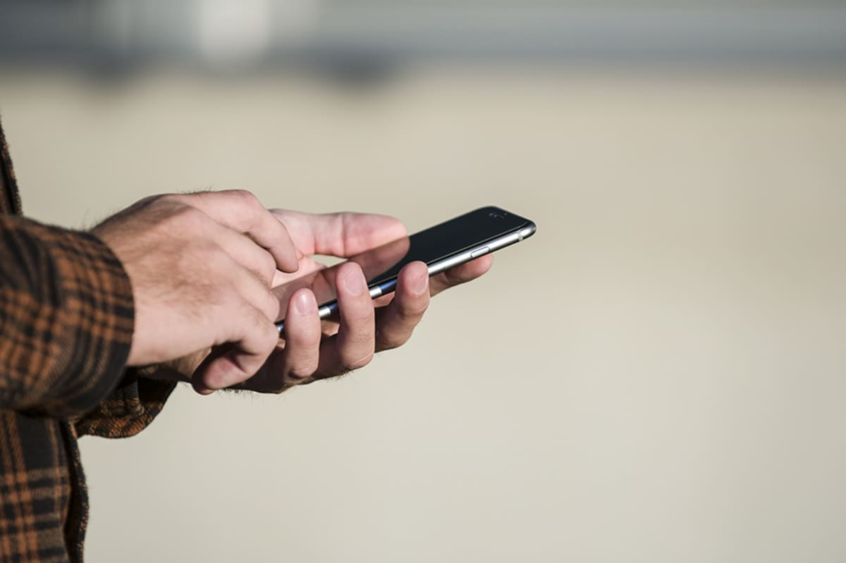 Henkilö käyttää älypuhelinta.