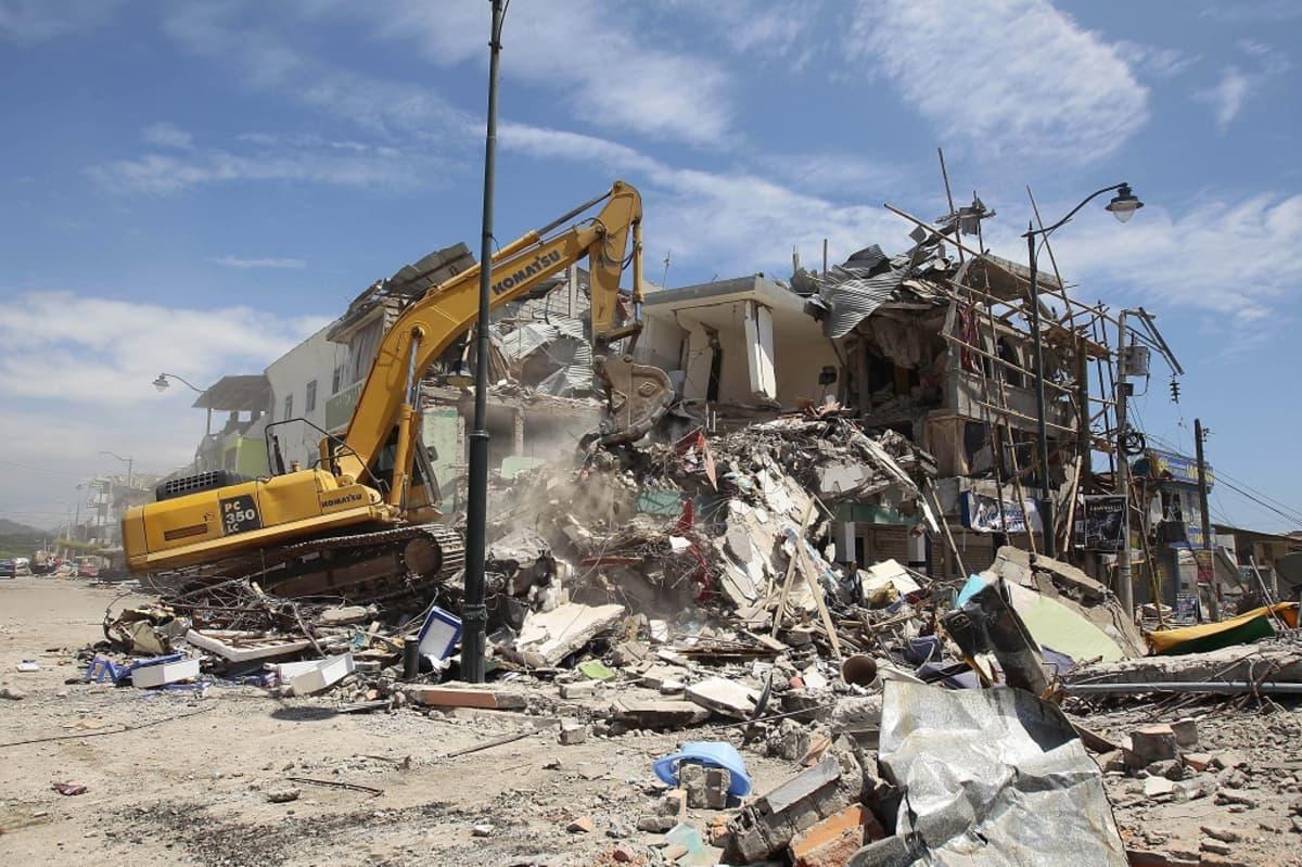 Kauhakuormaaja raivaamassa romahtaneen kaksikerroksisen talon raunioita.