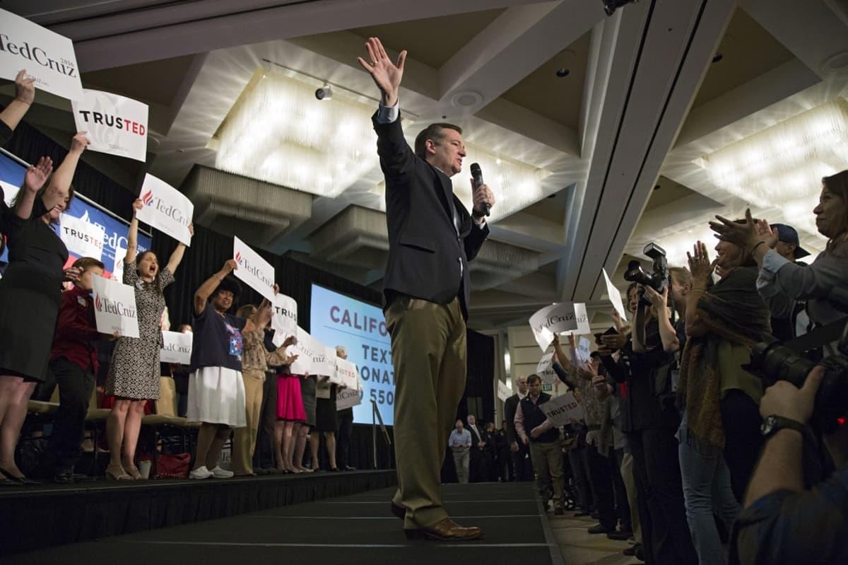 Ted Cruz puhuu vasemmassa kädessään olevaan mikrofoniin ja viittilöi oikealla kädellään jonnekin kauas. Kuva on otettu alaviistosta. Cruzin takana seissoo naisia, jotka pitävät käsissään hänen kampanjajulisteitaan.