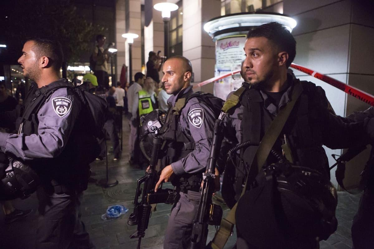 Kolme raskaasti aseistaunutta turvallisuusjoukkojen jäsentä kulkee kadulla.