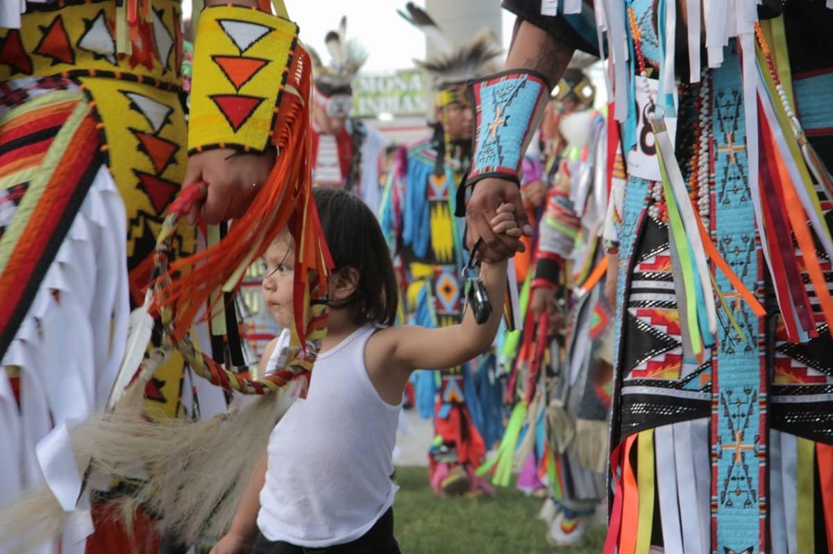 Intiaanilapsi pitää aikuista kädestä kiinni rituaalitanssin aikana. Intiaanit kokoontuvat joka vuosi pow wow -juhliin, joissa tanssi jatkuu yöhön asti.