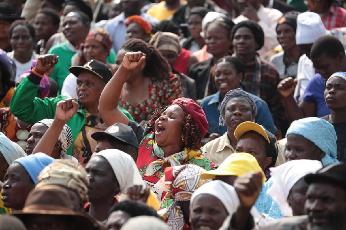 Kuvassa Mugaben kannattajia marssimassa Zimbabwen pääkaupungissa Hararessa.