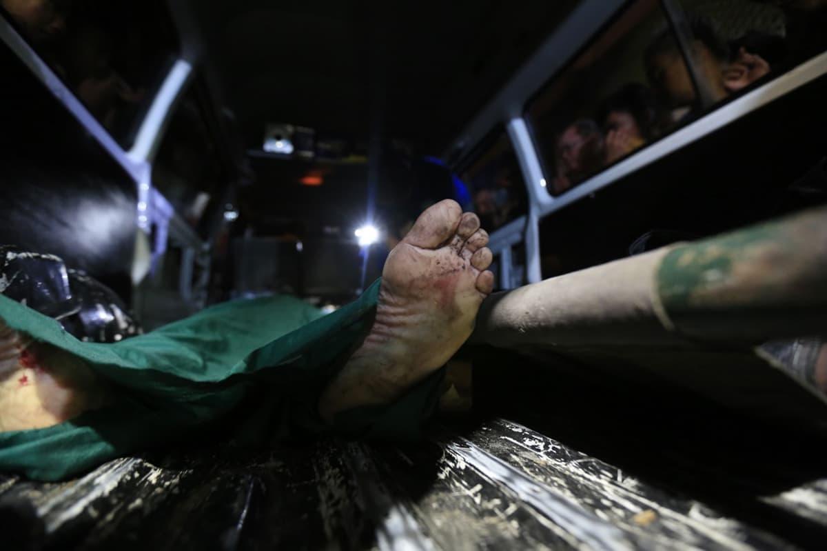 Ruumiin jalkapohja pilkottaa vihreän kankaan alta.
