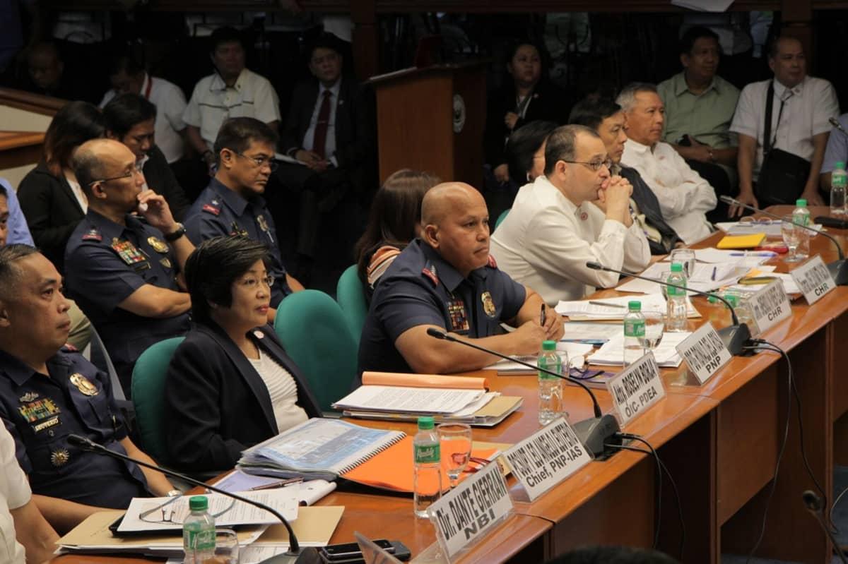 Useita ihmisiä senaatin istunnossa, istuvat pitkien pöytien ääressä riveittäin. Dela Rosa keskellä.