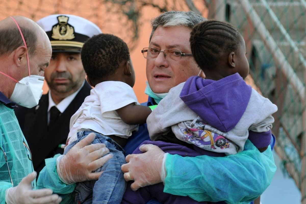 Lääkäri kantaa sylissään kahta pelastettua lasta.
